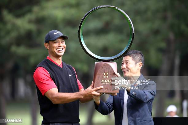 Tiger Woods of the United States receives the trophy from the Zozo founder Yusaku Maezawa at the award ceremony following the final round of the Zozo...