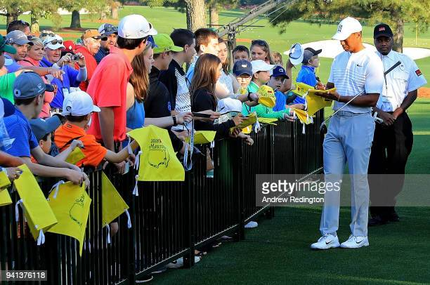 Tiger Woods of the United States signs autographs during a practice round prior to the start of the 2018 Masters Tournament at Augusta National Golf...