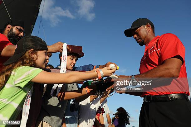 Tiger Woods of the United States signs autographs for young fans following the final round of the Hero World Challenge at Albany The Bahamas on...