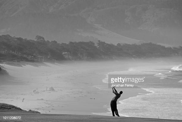 Tiger Woods of the United States silhouetted against the oceanside backdrop as he plays from the ninth fairway during the the 100th United States...