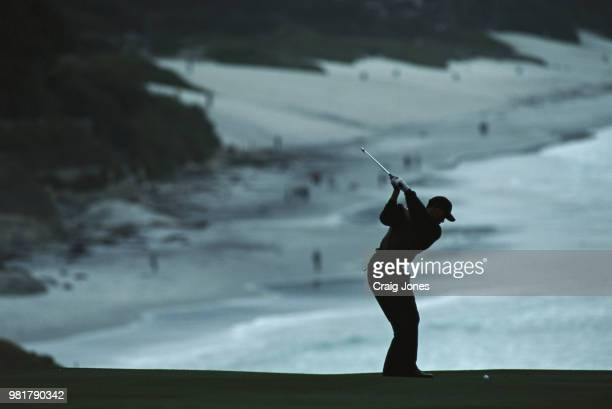 Tiger Woods of the United States silhouetted against the oceanside backdrop as he plays from the ninth fairway during the ATT Pebble Beach ProAm golf...