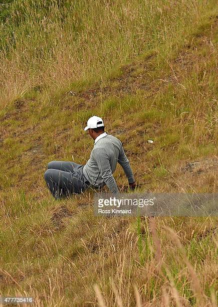 Tiger Woods of the United States slips in the rough near the tenth green during the second round of the 115th U.S. Open Championship at Chambers Bay...