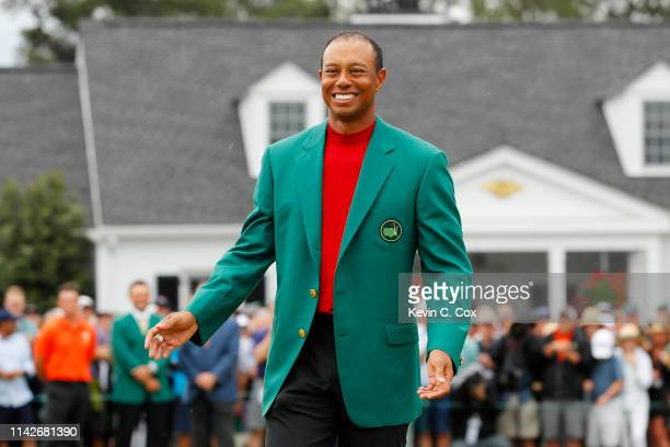 Tiger Woods of the United States smiles after being awarded the Green Jacket during the Green Jacket Ceremony after winning the Masters at Augusta...
