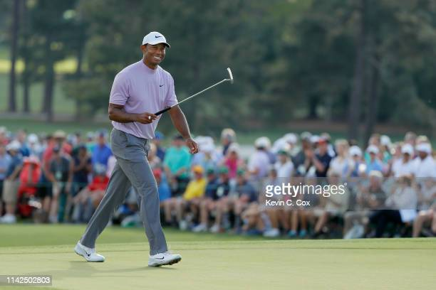 Tiger Woods of the United States smiles as he walks on the 18th hole during the third round of the Masters at Augusta National Golf Club on April 13...