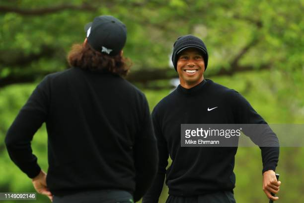 Tiger Woods of the United States smiles with Pat Perez of the United States on the practice green during a practice round prior to the 2019 PGA...