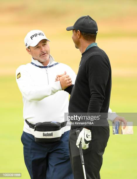 Tiger Woods of the United States speaks to Billy Foster caddie for Lee Westwood of England during previews to the 147th Open Championship at...