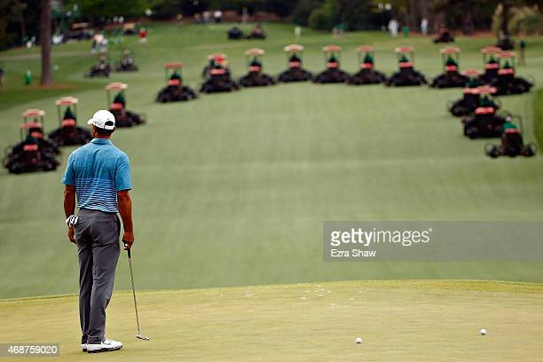 Tiger Woods of the United States stands on the green as grounds crew mow the the fairways during a practice round prior to the start of the 2015...