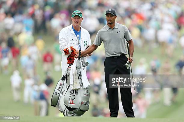 Tiger Woods of the United States stands with caddie Joe LaCava on the first hole during the first round of the 2013 Masters Tournament at Augusta...