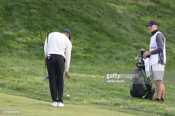 Tiger Woods of the United States takes a drop on the 18th hole as caddie Joe LaCava looks on during the second round of the 120th U.S. Open...