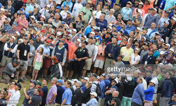 Tiger Woods of the United States takes his second shot on the 12th green as a gallery of fans look on during the second round of the 2018 US Open at...