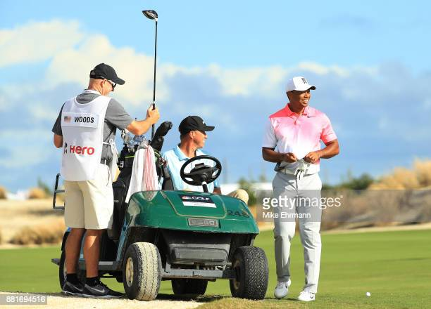 Tiger Woods of the United States talks to caddie Joe LaCava and Golf Channel reporter Jim 'Bones' Mackay during the proam prior to the Hero World...