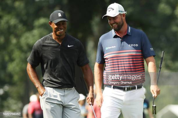 Tiger Woods of the United States talks to Marc Leishman of Australia during the second round of The Northern Trust on August 24 2018 at the Ridgewood...