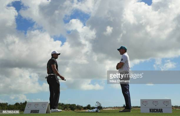 Tiger Woods of the United States talks to Matt Kuchar of the United States as they warm up on the range for the first round of the Hero World...