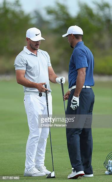 Tiger Woods of the United States talks with Brooks Koepka of the United States on the practice range during round two of the Hero World Challenge at...