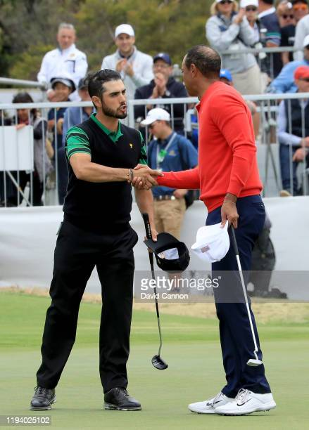 Tiger Woods of the United States Team shakes hands with Abraham Ancer of the International Team after he had won his match on the 16th green during...