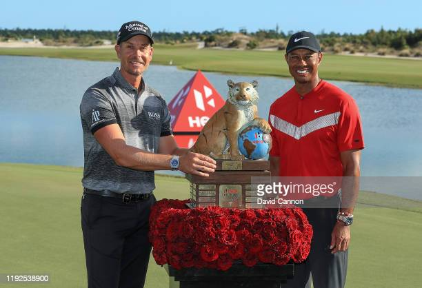 Tiger Woods of the United States the tournament host presents Henrik Stenson of Sweden with the trophy after the final round of the 2019 Hero World...