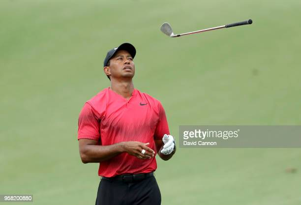 Tiger Woods of the United States tosses his wedge in frustration after his second shot on the par 4 14th hole spun back off the green during the...