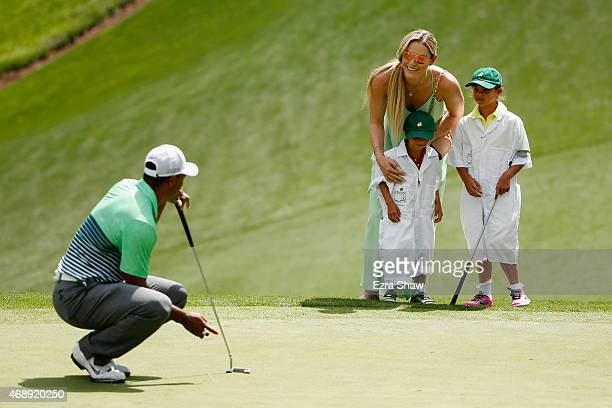 Tiger Woods of the United States waits a green as his girlfriend Lindsey Vonn, son Charlie and daughter Sam look on during the Par 3 Contest prior to...