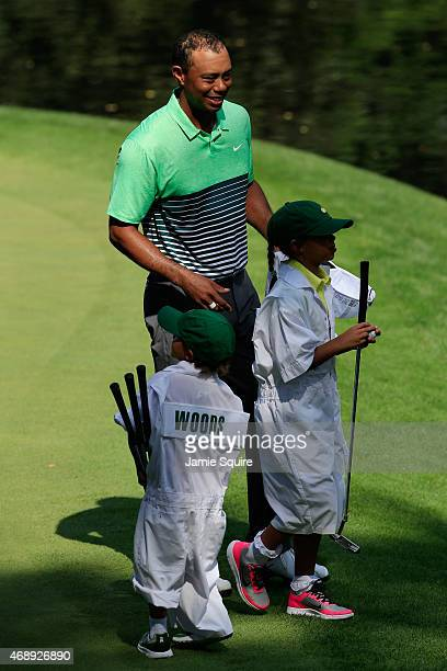 Tiger Woods of the United States waits with his son Charlie and daughter Sam during the Par 3 Contest prior to the start of the 2015 Masters...