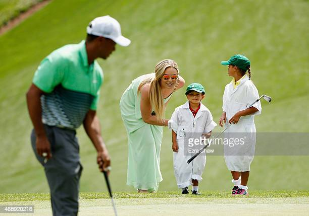 Tiger Woods of the United States walks across a green as his girlfriend Lindsey Vonn, son Charlie and daughter Sam look on during the Par 3 Contest...