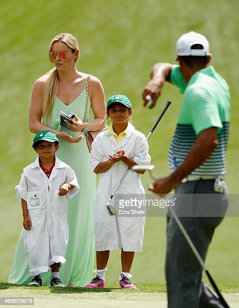 Tiger Woods of the United States walks across a green as his girlfriend Lindsey Vonn son Charlie and daughter Sam look on during the Par 3 Contest...