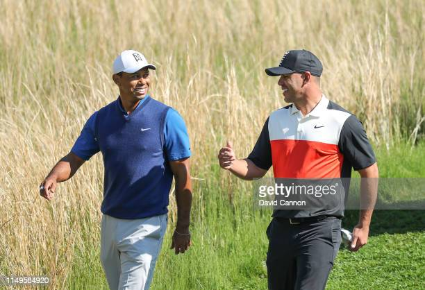 Tiger Woods of the United States walks off the 13th tee with his playing partner Brooks Koepka of the United States during the first round of the...