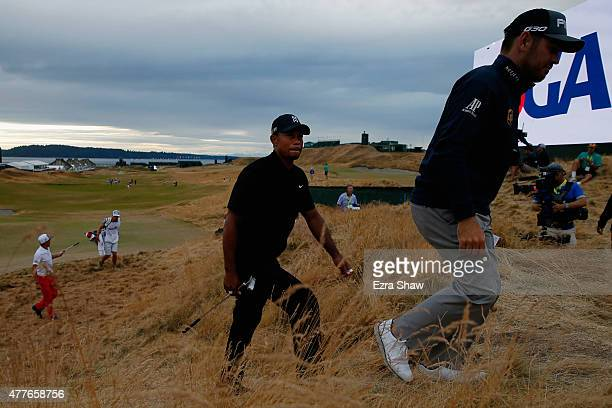 Tiger Woods of the United States walks off the 18th green after completing the first round of the 115th U.S. Open Championship at Chambers Bay on...