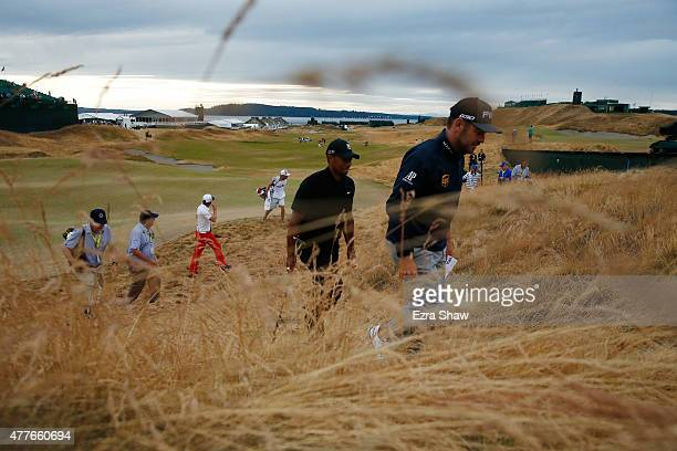 Tiger Woods of the United States walks off the 18th green after completing the first round of the 115th US Open Championship at Chambers Bay on June...