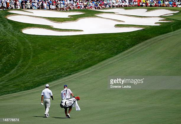 Tiger Woods of the United States walks up the fifth fairway with caddie Joe LaCava after hitting his approach shot during the first round of the...