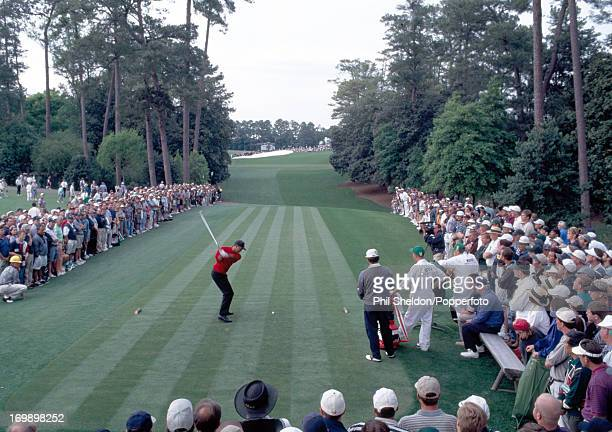 Tiger Woods of the United States watched by his playing partner Costantino Rocca of Italy and their caddies tees off on the 72nd fairway of the final...
