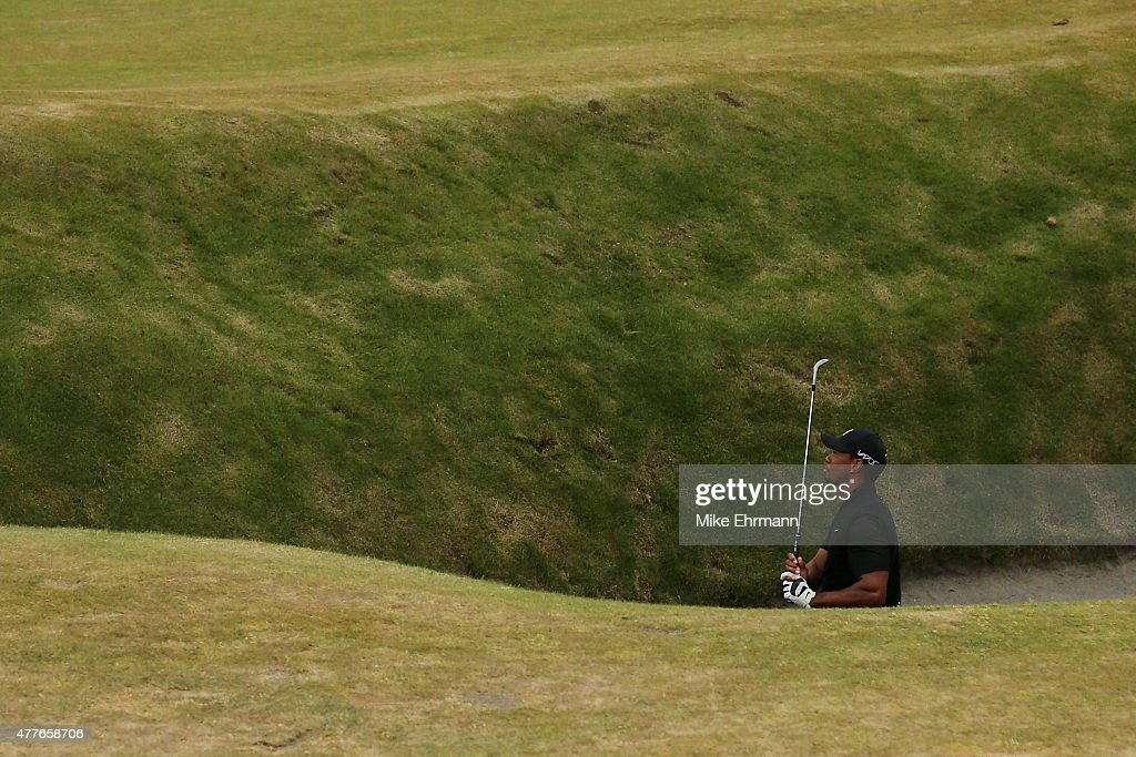 Tiger Woods of the United States watches his shot from a fairway bunker on the 18th hole during the first round of the 115th U.S. Open Championship at Chambers Bay on June 18, 2015 in University Place, Washington.