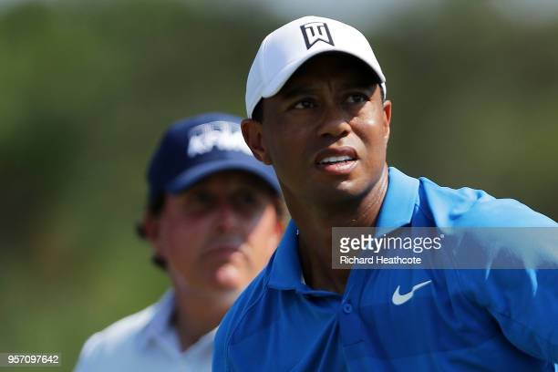 Tiger Woods of the United States watches his shot from the ninth tee as Phil Mickelson of the United States looks on during the first round of THE...