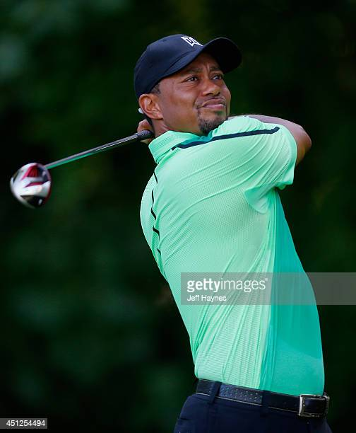 Tiger Woods of the United States watches his tee shot on the 14th hole during a first round of the Quicken Loans National at Congressional Country...