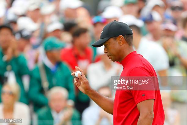 Tiger Woods of the United States waves after making par on the ninth green during the final round of the Masters at Augusta National Golf Club on...