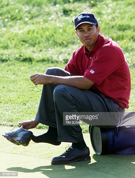 TIger Woods of the US and a member of the US team at the Presidents Cup golf competition sits on his bag as he readjusts one of his shoes during his...