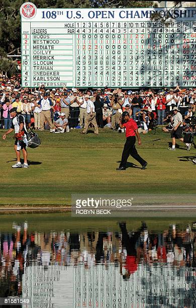 Tiger Woods of the US and his caddie Steve Williams walk past the leader board on their way to the 18th hole green in the fourth round of the 108th...