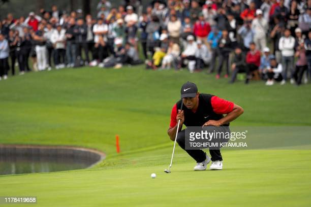 Tiger Woods of the US checks the line on the 5th hole green during the fourth round of the PGA Zozo Championship golf tournament at the Narashino...
