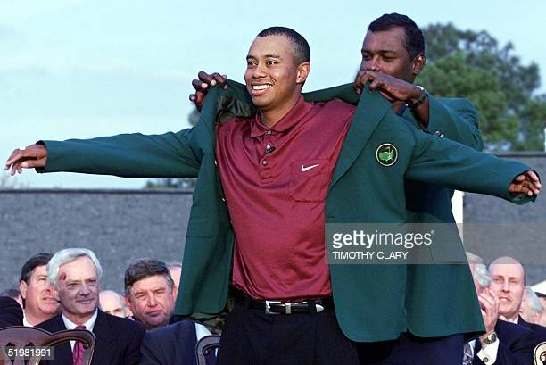 Tiger Woods of the US gets his second green jacket from 2000 Masters Champion Vijay Singh of Fiji 08 April 2001 during the final round of the 2001...