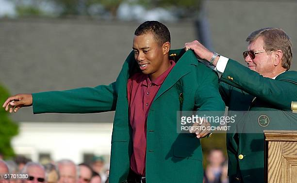 Tiger Woods of the US gets his third green jacket from tournament chairman Hootie Johnson 14 April 2002 after winning the 2002 Masters golf...