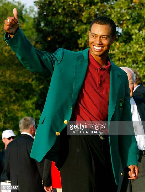 Tiger Woods of the US gives a thumbs up to the crowd after getting his third green jacket 14 April 2002 after winning the 2002 Masters golf...