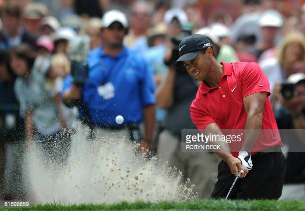 Tiger Woods of the US hits out of a bunker on the 11th hole fairway in the 108th US Open golf tournament playoff against compatriot Rocco Mediate at...