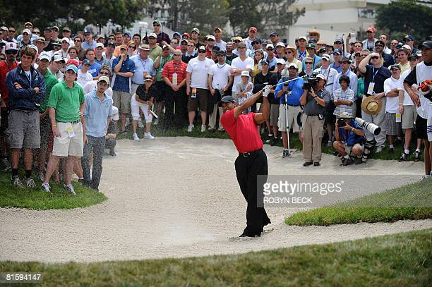 Tiger Woods of the US hits out of a bunker on the 14th hole fairway in the 108th US Open golf tournament playoff against compatriot Rocco Mediate at...