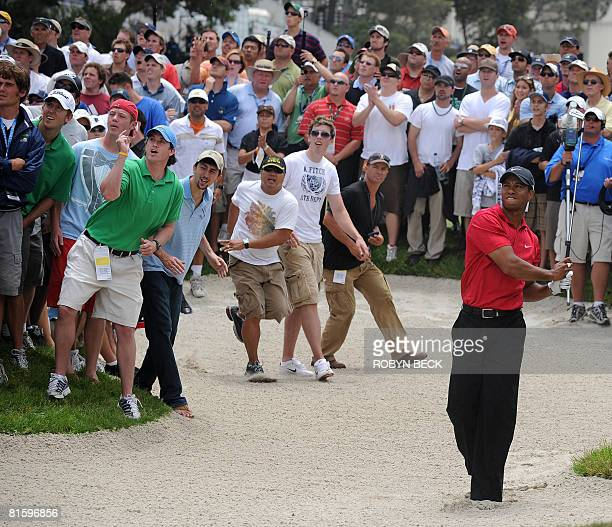 Tiger Woods of the US hits out of a bunker on the 14th hole fairway in the 108th US Open golf tournament playoff against fellow American Rocco...
