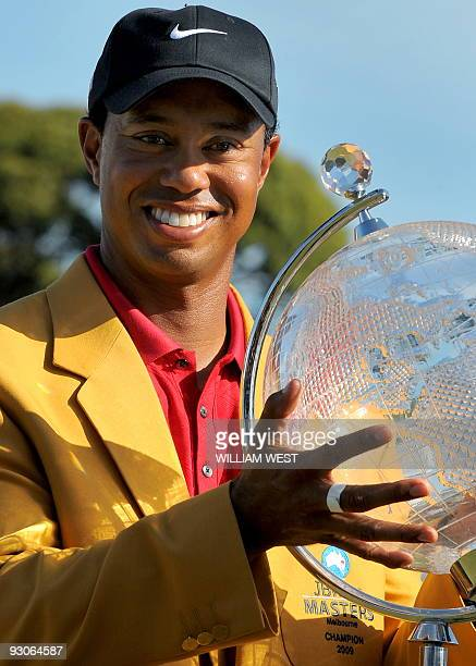 Tiger Woods of the US holds the trophy aloft after winning the Australian Masters golf tournament at the Kingston Heath course in Melbourne on...