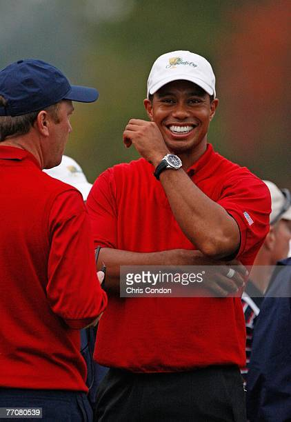 Tiger Woods of the U.S. Jokes with Assistant captain Jeff Sluman on th 18th green during the first round of competition for The Presidents Cup on...