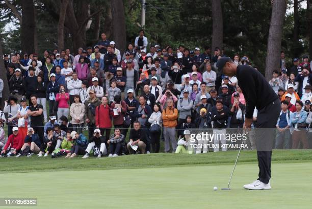 Tiger Woods of the US putts on the 5th hole green during the first round of the Zozo Championship golf tournament at the Narashino Country Club in...