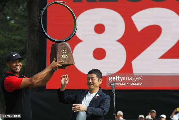 TOPSHOT Tiger Woods of the US receives a victory trophy from Yusaku Maezawa the founder of Zozo during the awarding ceremony of the PGA ZOZO...