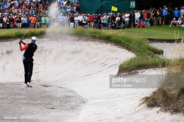Tiger Woods of the US Team hits an approach shot from a greenside bunker on the 15th hole during the Day Four Singles Matches of the 2011 Presidents...