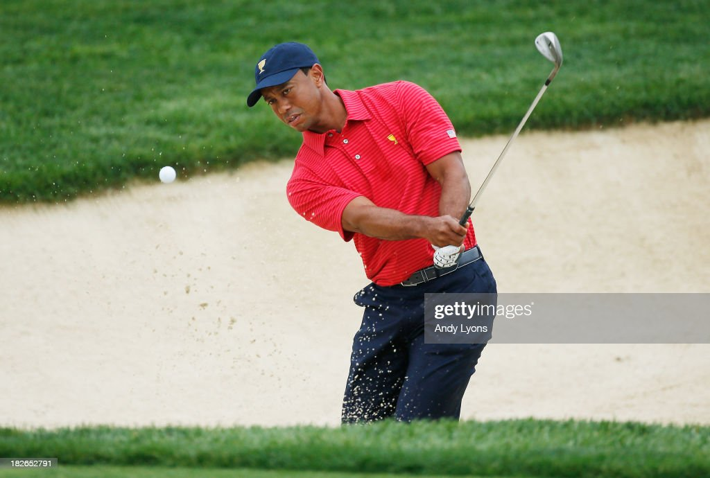 Tiger Woods of the U.S. Team plays a bunker shot during a practice round prior to the start of The Presidents Cup at the Muirfield Village Golf Club on October 2, 2013 in Dublin, Ohio.