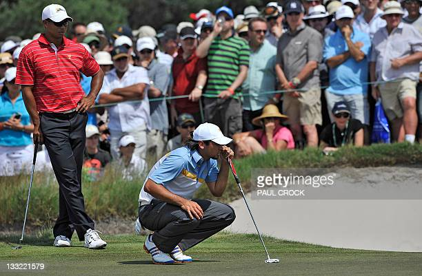 Tiger Woods of the US team watches on as Jason Day of the International team lines up a putt during the President's Cup tournament match played at...